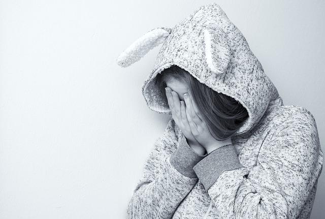 手で顔を覆う悩んだ女性
