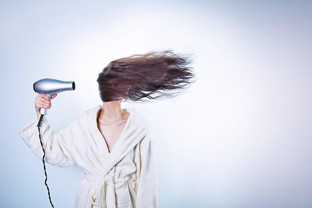 ドライヤーで髪がなびいている女性