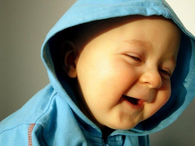 フードを被った笑顔の赤ちゃん