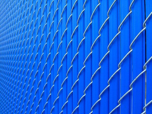 壁の様な青い柵と金網
