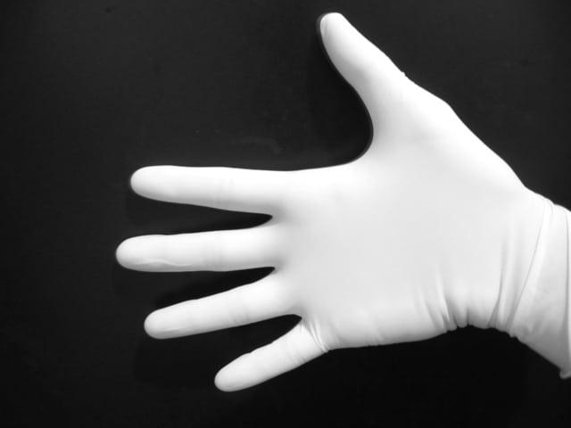 医療用手袋をはめた開いた右手