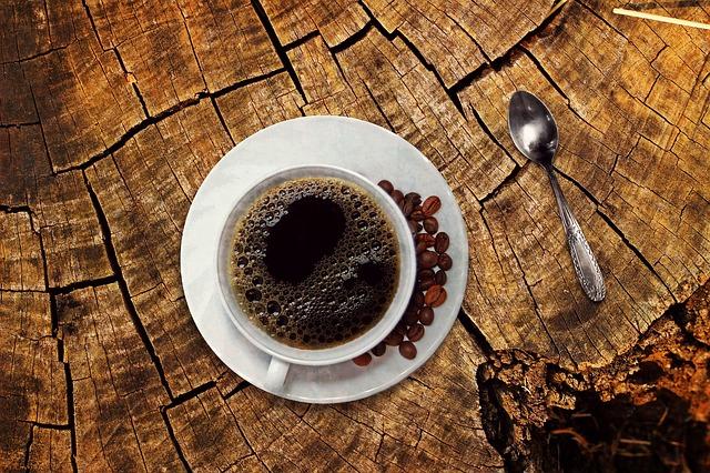 切り株の上に置かれたコーヒーとスプーン