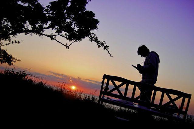 夕焼けの桟橋で何かを書く青年