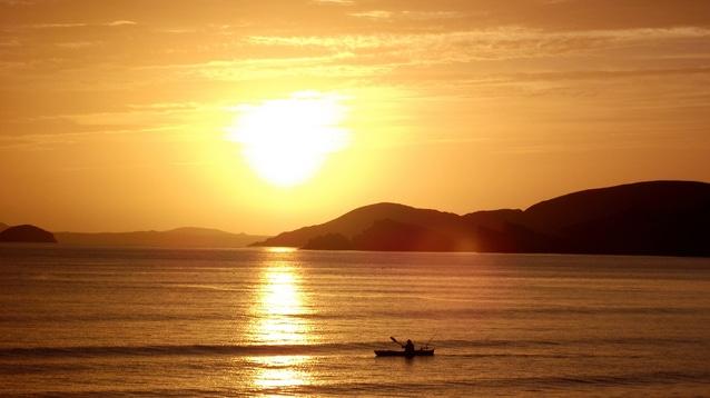 夕陽が沈む海に浮かんでいる小舟