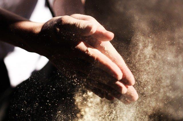 小麦粉をはらうパン職人の手
