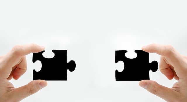 2つのジグソーパズルを持って合わせようとしている手