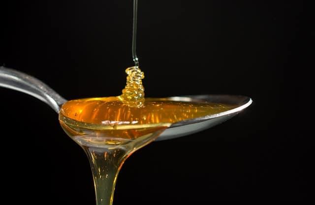 溢れ出すスプーンに落ちてくる蜂蜜