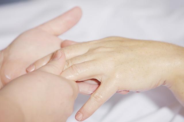 指のマッサージを受けている女性の手