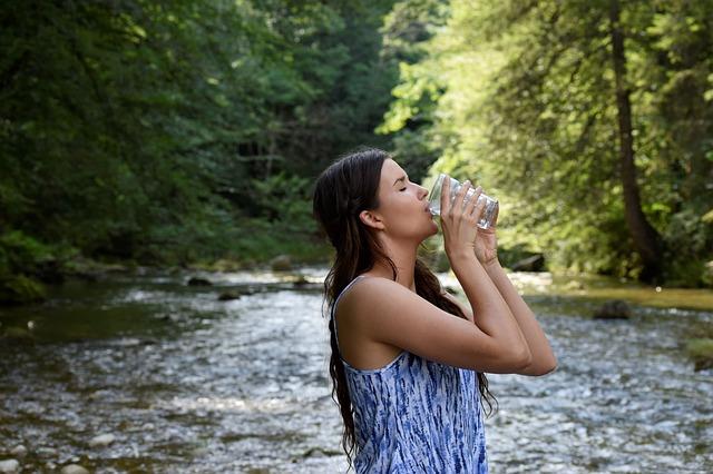 河でコップから水を飲む女性