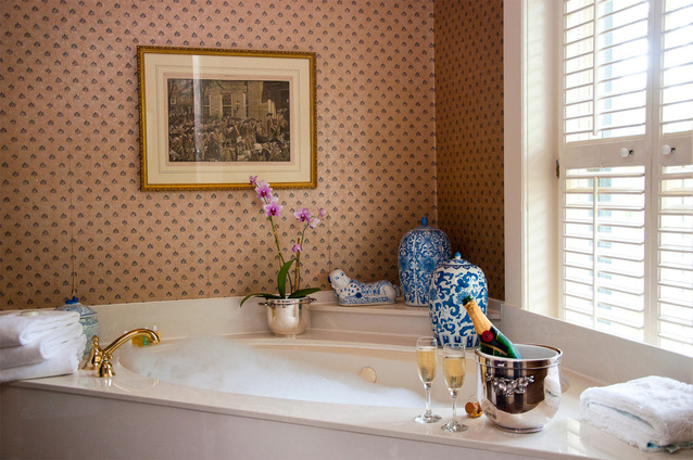 浴槽の側にあるシャンパンと2つのグラス