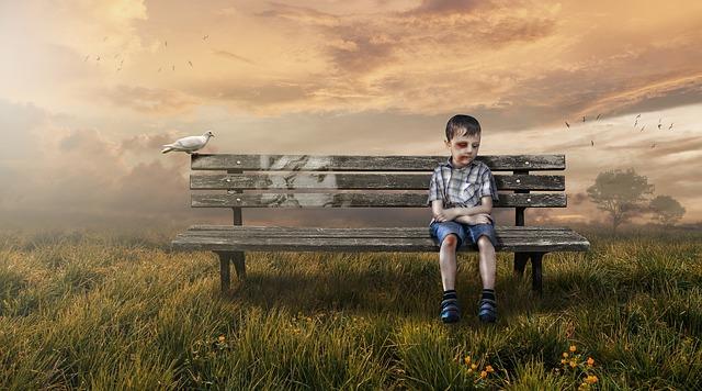 顔を腫らせたベンチに座る少年と鳩