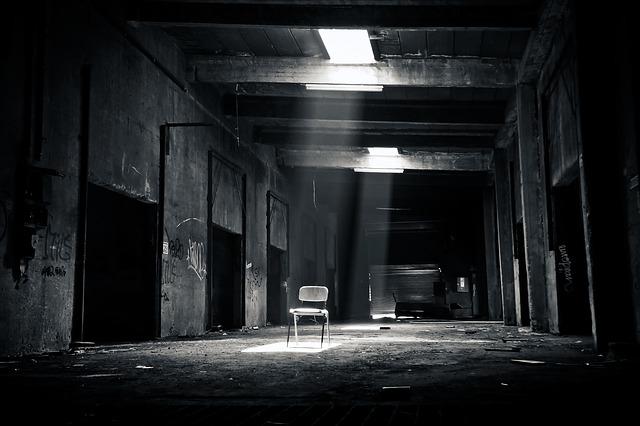 廃墟の天井から差し込む光に一脚の椅子