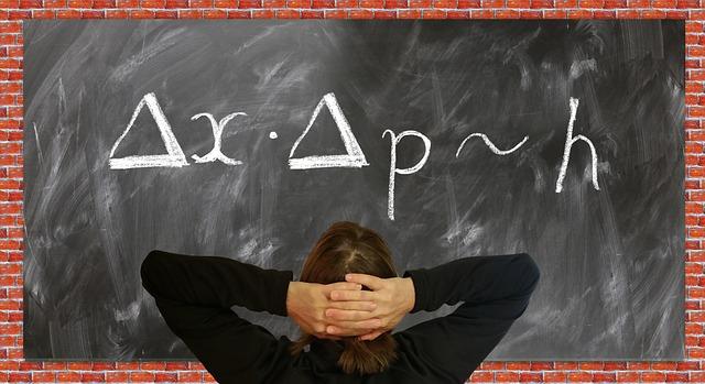 黒板に書かれた文字に頭を悩ませる女性