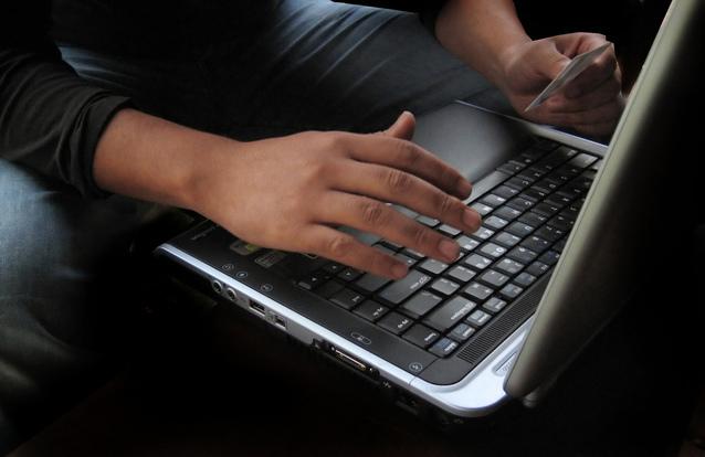 クレジットカードを片手にノートパソコンを打ち込む男性