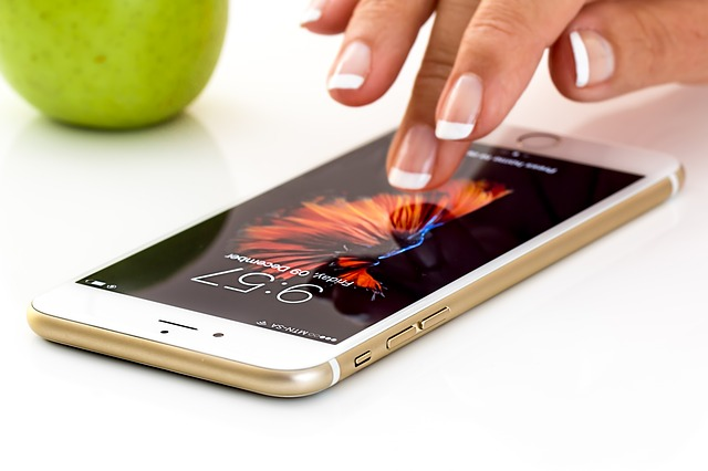 iPhoneを操作する女性の指と青りんご
