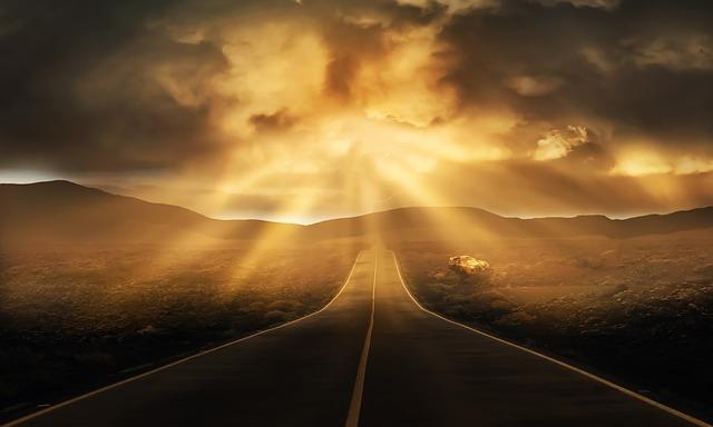真っ直ぐに伸びた道路の向こうに天から差す光