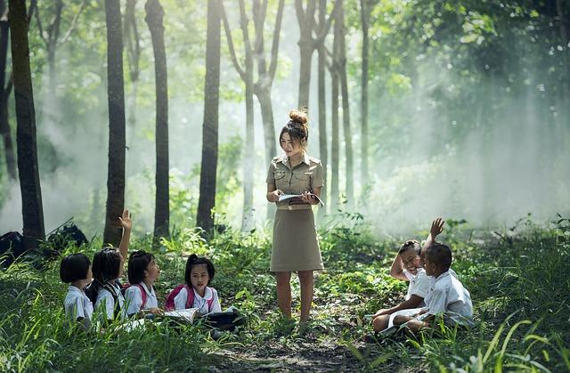 森の中で子供達に授業をする女性