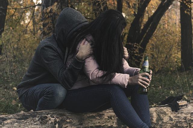 悲しげな女性の背中からそっと抱きしめる男性