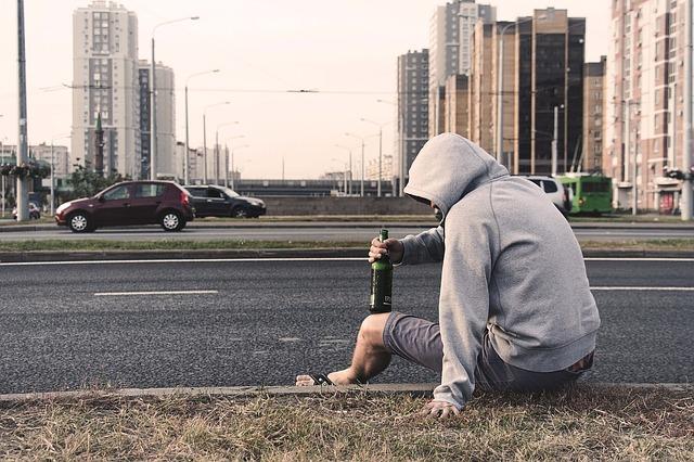 酒瓶を片手に幹線道路沿いに座る男性