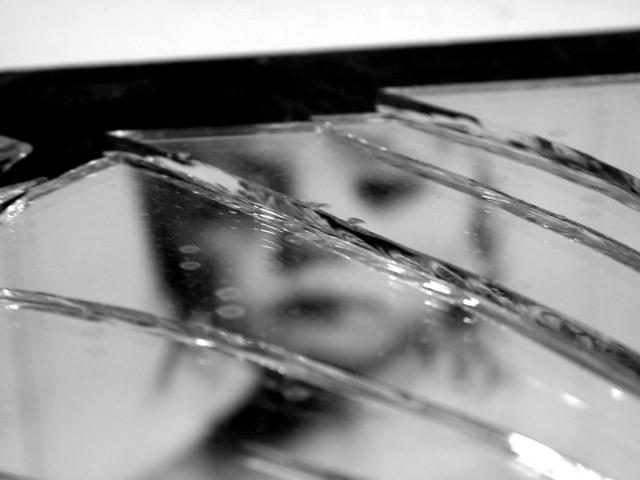 割れた鏡に映る寂しげな少女