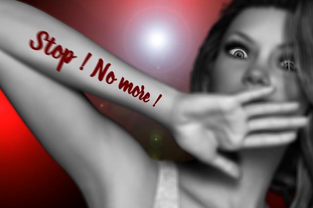 恐怖に怯えた女性が静止する腕にStop!NoMore!と記載