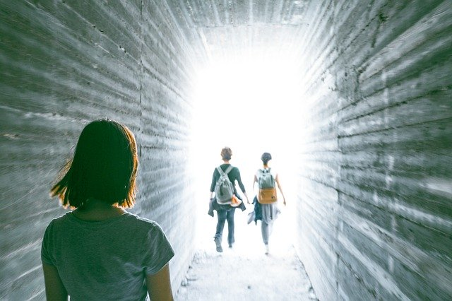 洞窟から外の光へ歩く少年二人をじっと見つめる少女