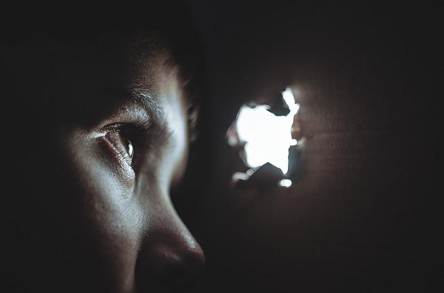 真っ暗な空間にいる少年が小さな穴から外を覗く