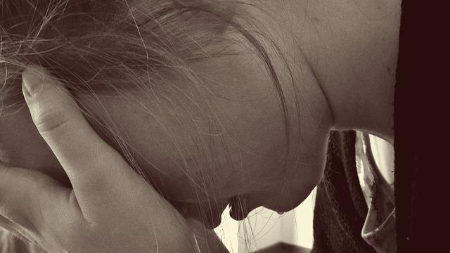 少女がうつむき両手で顔を隠す