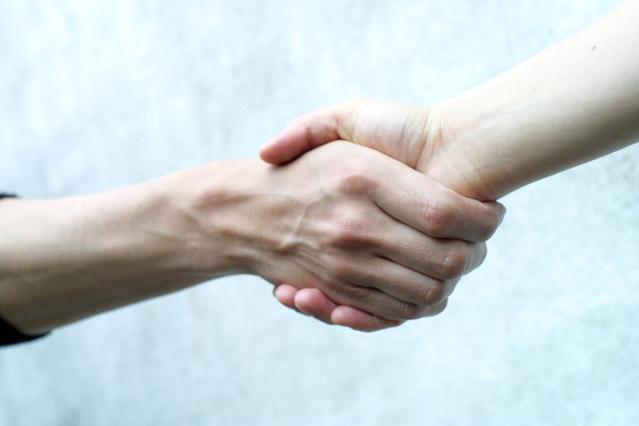 固く握手をする男女