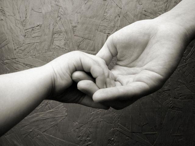 母が我が子に手を差し出しぎゅっと握る