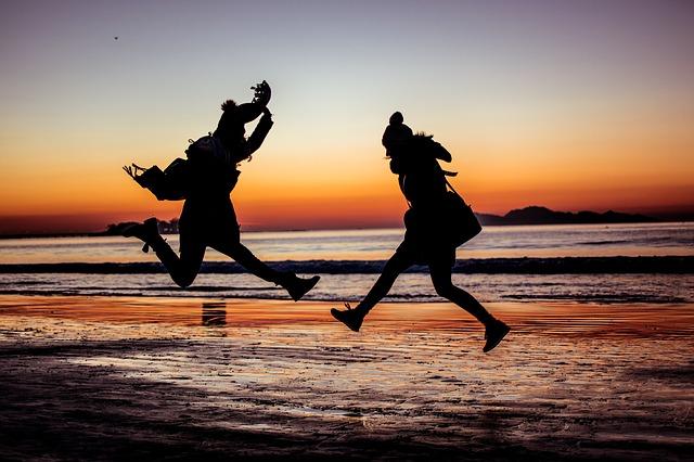 夕方の海岸でジャンプしている二人の女性