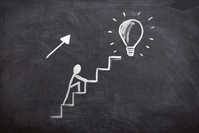 黒板に書かれたひらめきへの階段を登る人