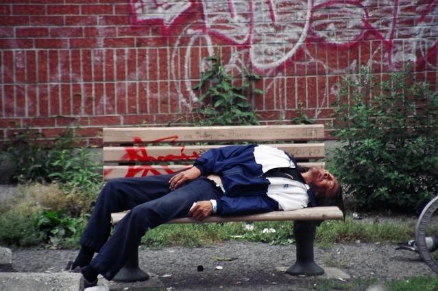 ベンチで寝ている中年男性