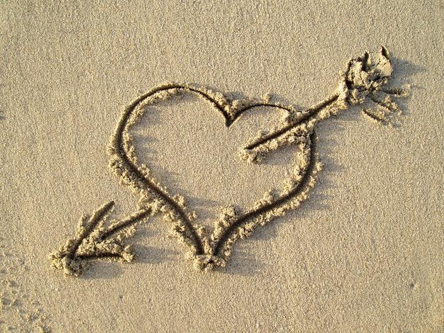砂浜に書かれたハートに矢が刺さる