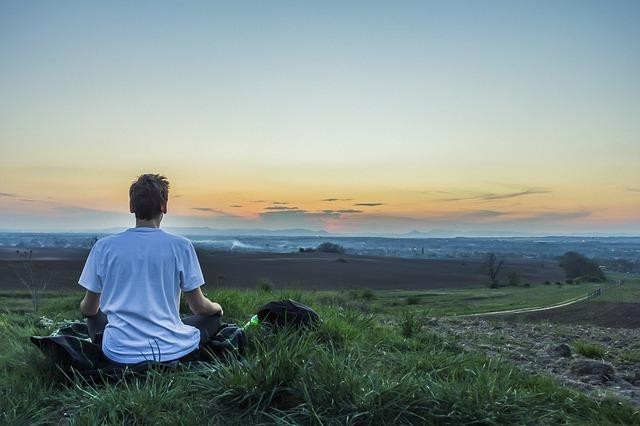 広大な大地で瞑想をする男性の後ろ姿