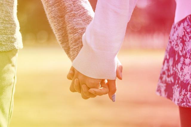 淡い色合いで手を繋ぐ若い男女