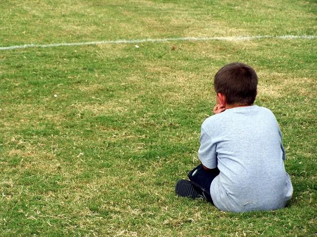 グラウンドに独り寂しく座る少年