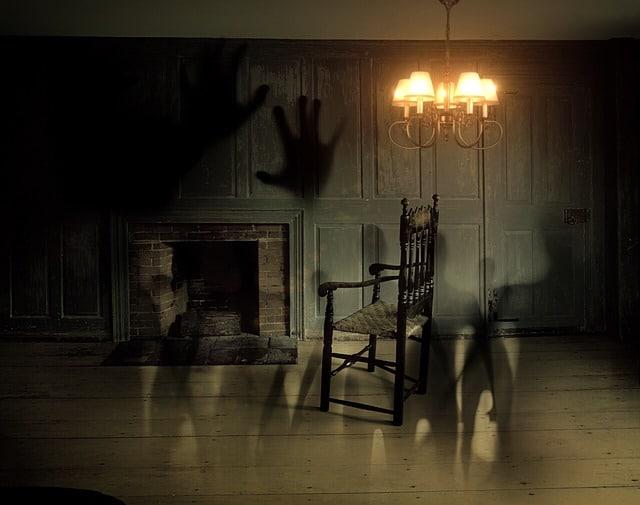 暖炉のある暗い洋室に様々な人の影