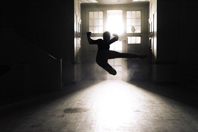 室内で飛び蹴りをしている人のシルエット