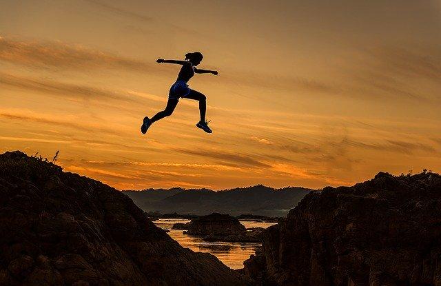 崖から崖へジャンプしている女性の合成画像