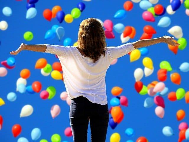 カラフルな風船が数多く飛ぶ中で両手を広げる女性の後ろ姿