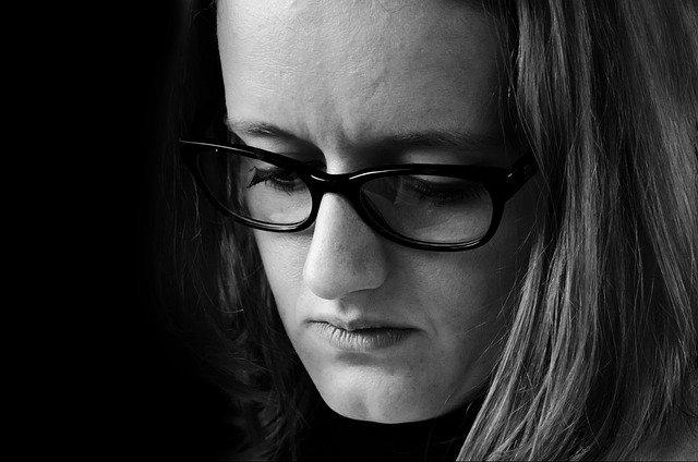 思い悩む眼鏡を掛けた女性