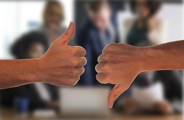 会議をしている前で親指を立てているのと下げているの