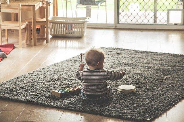 カーペットの上で太鼓で遊ぶ赤ちゃん