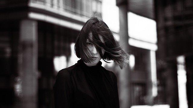 紙を風になびかせる女性がじっと見つめている