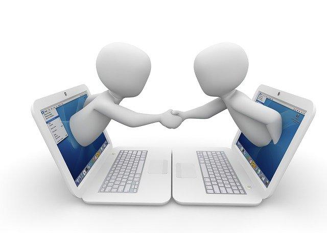 互いのノートパソコンのモニターから出て握手をするピクトグラム