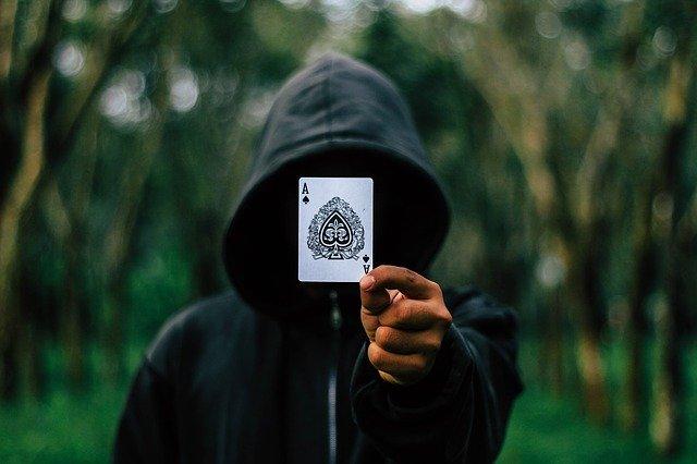 エースのカードで顔を隠す怖い人