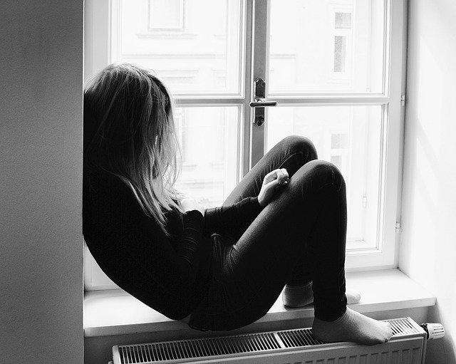 出窓に座る落ち込んだ女性