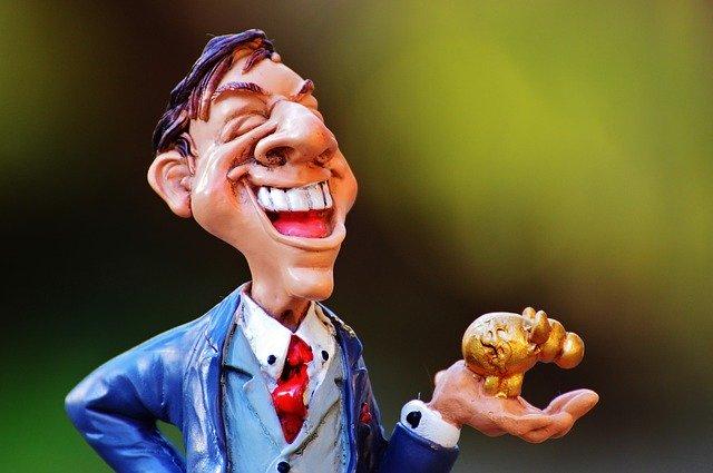 手の上に金色の置物を持つ笑顔の男性の人形