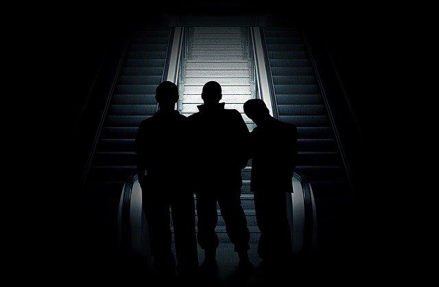 エレベーター前に立つ三人の男性シルエット